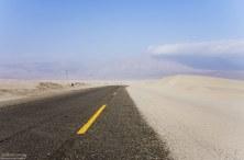 Песок с белоснежных дюн частично заползает на дорогу.
