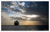 """Круизное судно """"Mariner of the Seas"""" у берегов острова на закате."""