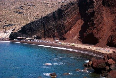 Красный пляж под гигантским утесом. Одежда - опционально .