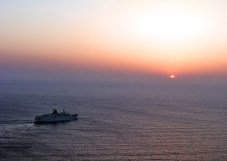 Солнце в закатной дымке и круизное судно.