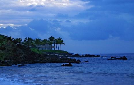 Сумерки над островом и вилла в пальмах на берегу.