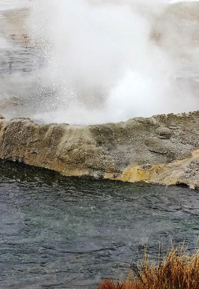 Небольшой гейзер на берегу реки. Biscuit basin.