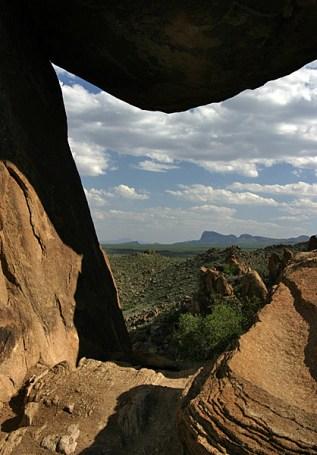 Вид на пустыню через окно, образованное балансирующей скалой.