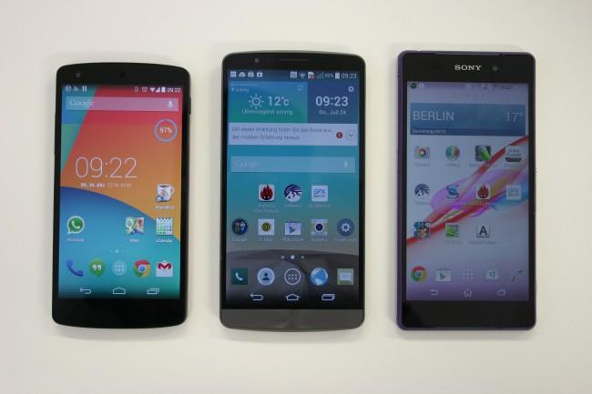 """Was auffällt: Die extrem schmalen Ränder des LG G3 (Mitte). Das Sony Xperia Z2 (rechts) hat beinahe exakt die selben Abmessungen (B&H), bringt dabei aber """"nur"""" 5,2 Zoll Bildschirmdiagonale mit. Das LG G3 bietet dagegen 5,5 Zoll. Auch das kleinere Google Nexus 5 (ebenfalls von LG gefertigt) weist deutlich breitere Ränder auf."""