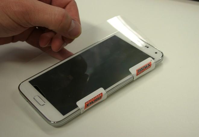 Applikation: Das gerade Auftragen der Folie ist nichts für zittrige Finger. Das Produkt von Displex wird dazu seitlich mit Klebestreifen fixiert.