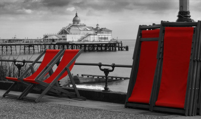 Enhanced black and white photograph of Brighton pier in the centre with a foreground of the promenade, two deckchairs ready for seating and several stacked deckchairs. All deckchair covers are picked out in blood red.  © Copyright 2014 Andy Huntley photography