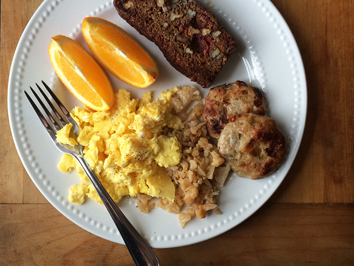Scrambled eggs, cauliflower hash, homemade apple-onion chicken breakfast sausage, and toasted grain-free cranberry-pecan bread.