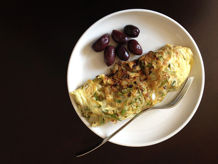 Zucchini, onion, and garlic omelet with black olives on the side