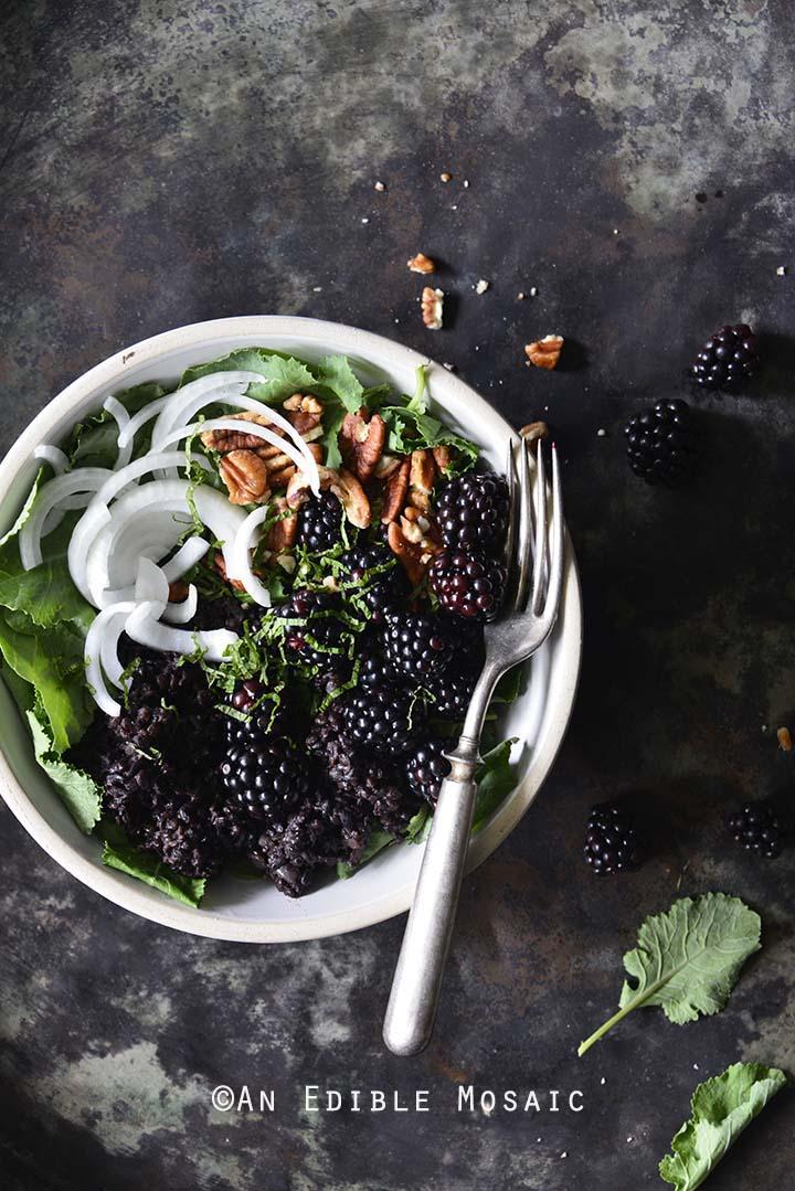 Vegan Herbed Black Rice, Black Lentils, and Black Quinoa Pilaf Salad Bowls with Blackberries on Weathered Metal Background Top View Vertical Orientation