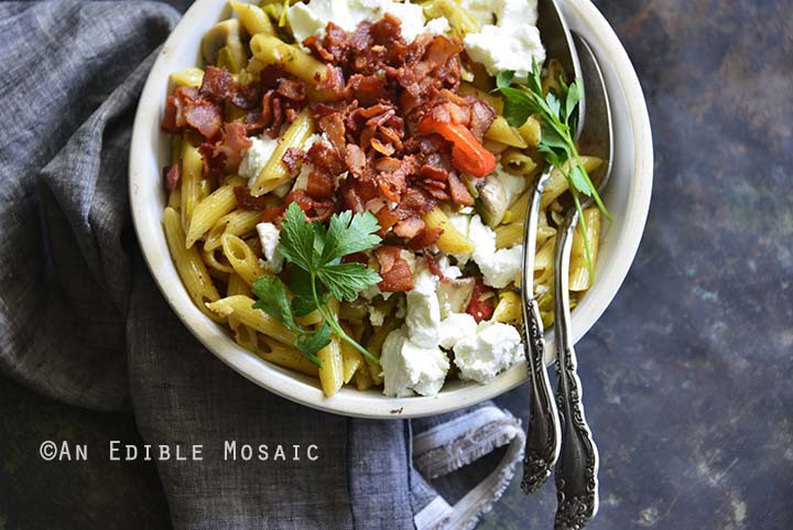 Warm Caramelized Leek Pasta Salad with Bacon and Goat Cheese on Metal Background