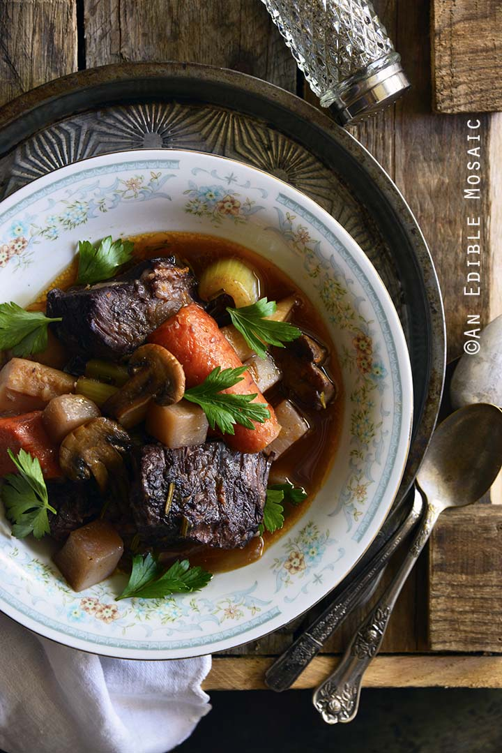 Braised Beef with Root Vegetables and Red Wine on Wooden Table Top View Vertical Orientation