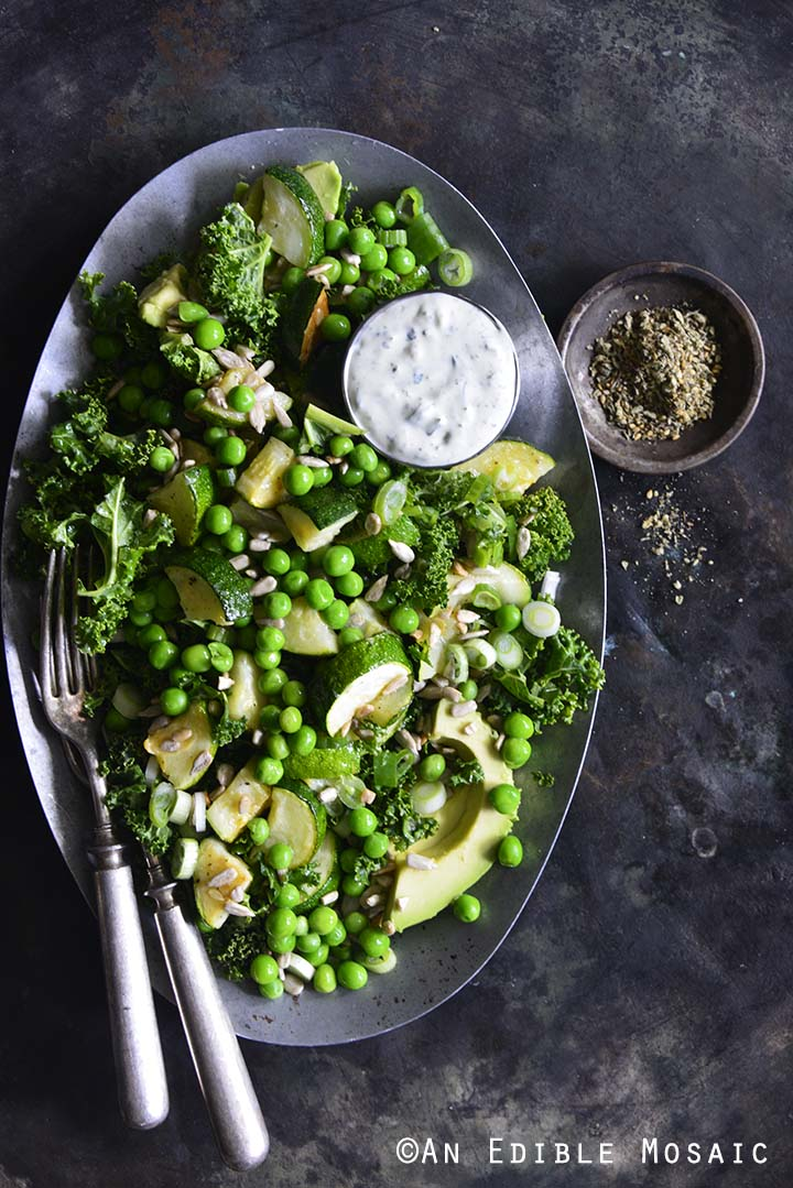 Kale, Roasted Zucchini, and Green Pea Salad with Creamy Za'atar Dressing on Vintage Metal Tray