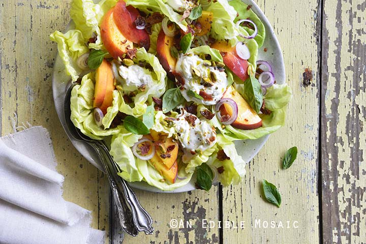 Plate of Burrata Peach Salad with Butter Lettuce, Basil, and Pistachio with White Linen