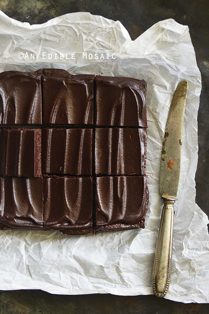 Overhead View of Fudgy Guinness Brownies with Dark Chocolate Ganache Recipe on Parchment Paper on Metal Background