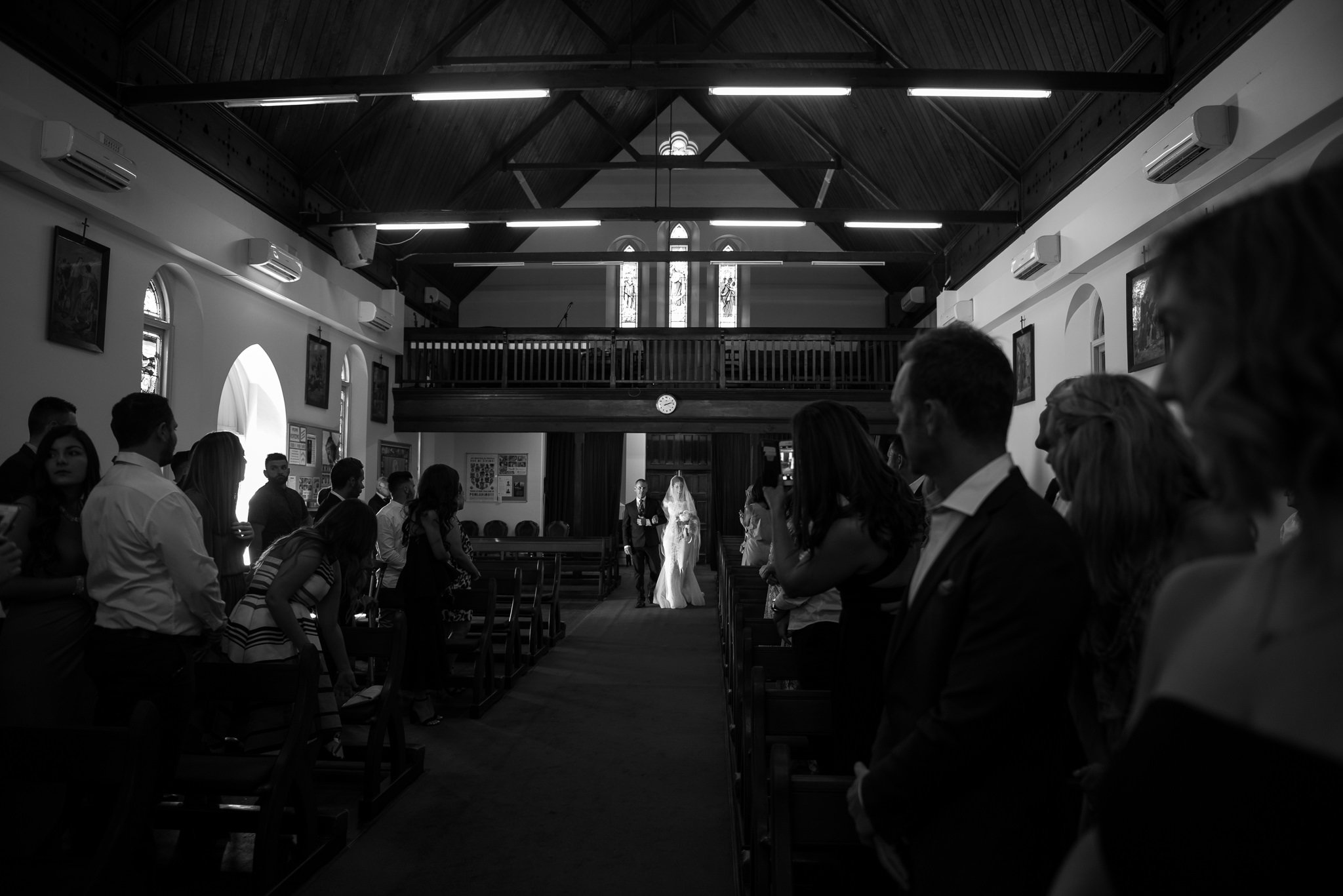 bride and father walking into dark church