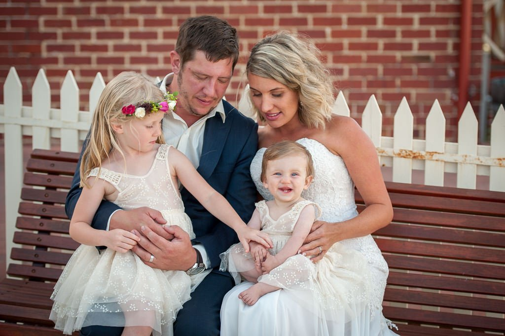 bride and groom with their little family