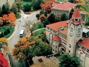 Photo shows a close aerial view of the University of Kansas, Lawrence, campus with limestone buildings and red tile roofs.