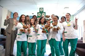 """A group of smiling health care workers give the two-fingered Hawaiian """"hang loose"""" sign. Some of them might make ideal foster parents, especially for children with medical needs."""