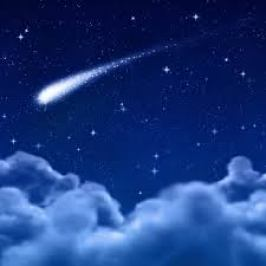 A dark-blue, realistic image of a comet, on background of stars, shooting across the sky above a bank of fluffy clouds