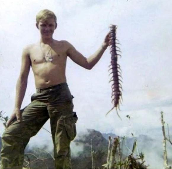 Fotografía de im soldado estadounidense sosteniendo un ciempiés vietnamita.