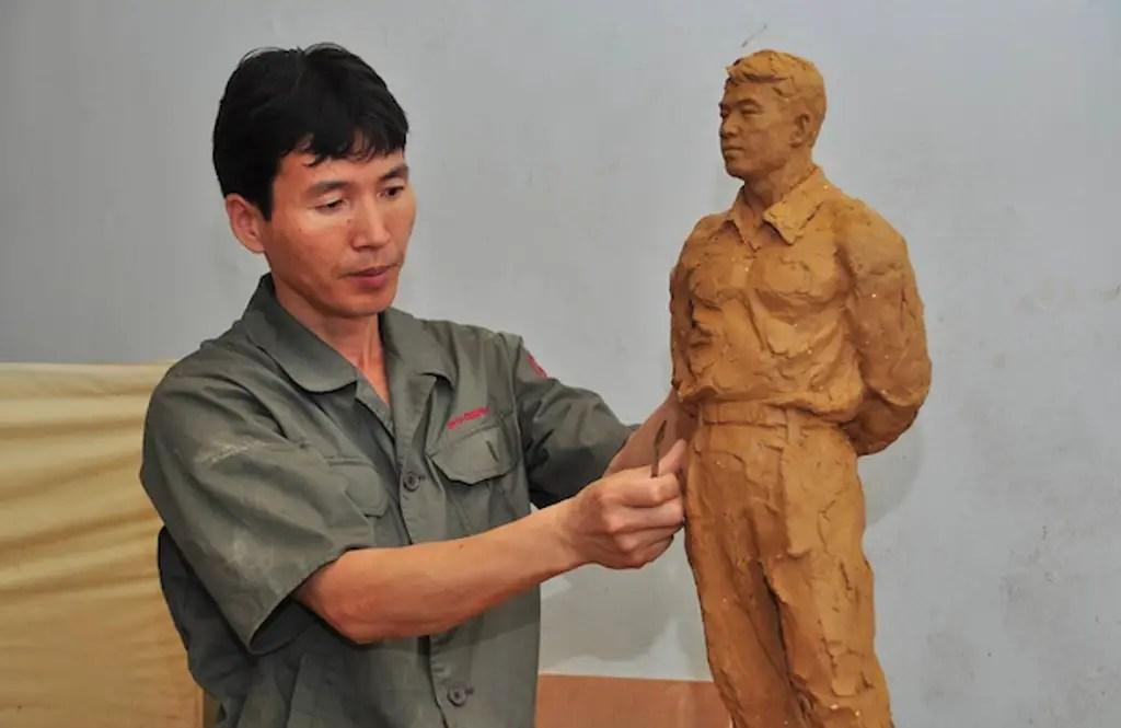 Fotografía de un escultor trabajando en una estatua.