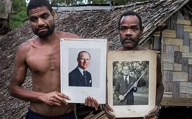 Dos hombres sosteniendo fotografía del Príncipe Felipe, vemos el efecto de los cargo cults.
