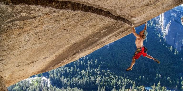 Fotografía de un hombre escalando una montaña sin cuerdas.