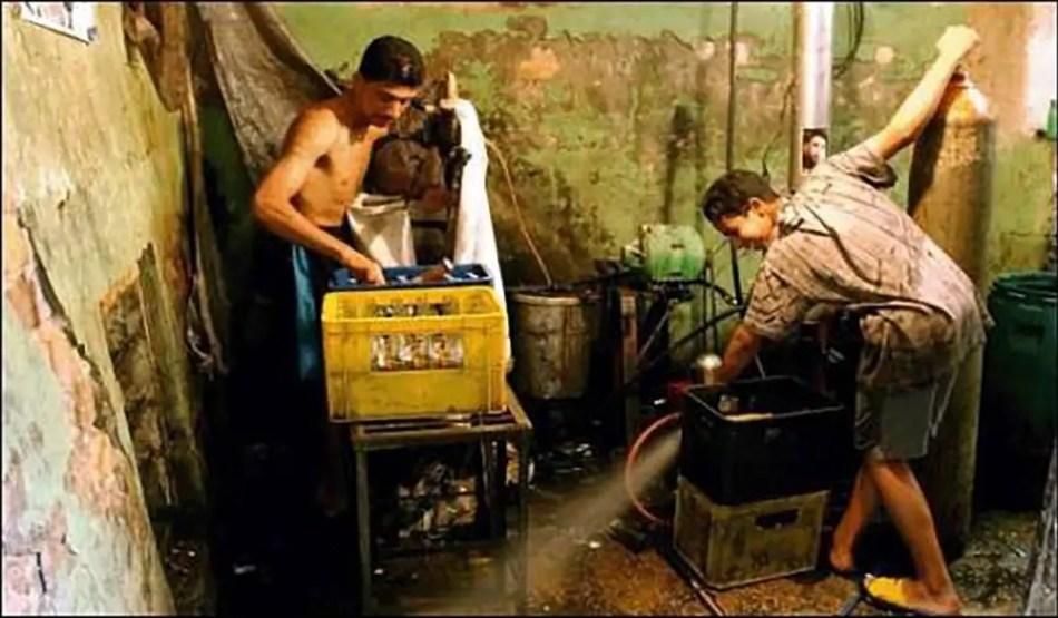 Operarios de la fábrica de pepsi clandestina limpiando preparando el CO2.
