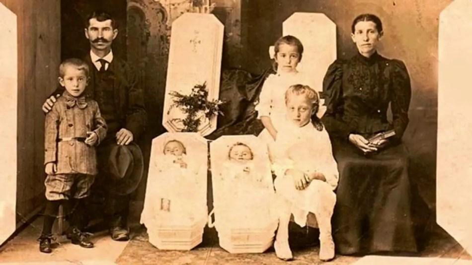 Una familia despidiendo a dos niños pequeños.