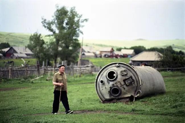Poblador de la región de Altái caminando cerca de un resto de cohete el cual fue arrastrado al pueblo para su desguace.