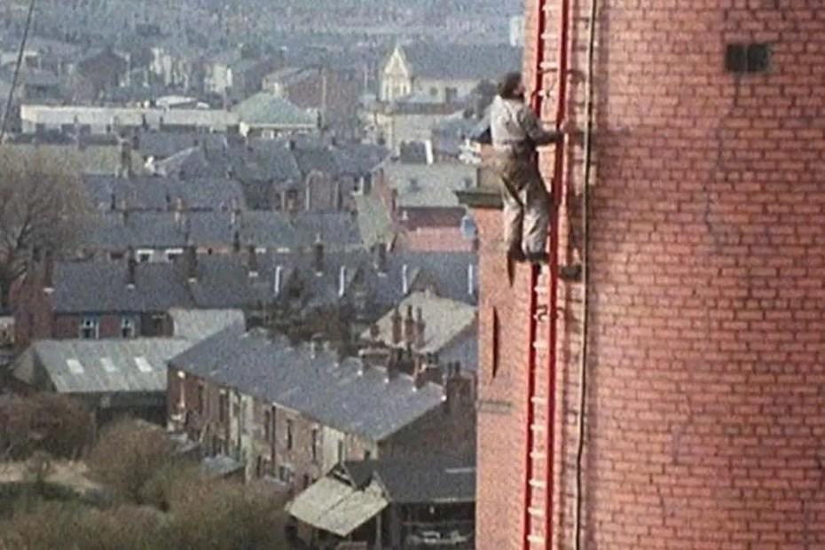 Fred Dibnah subiendo a lo largo de una alta chimenea.