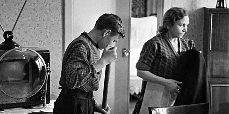 Madre e hijo juntos a uno de los televisores soviéticos con lentes de aumento KVN-49.