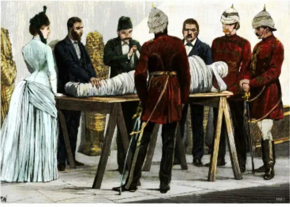 Oficiales y civiles observando una momia siendo desenrollada.