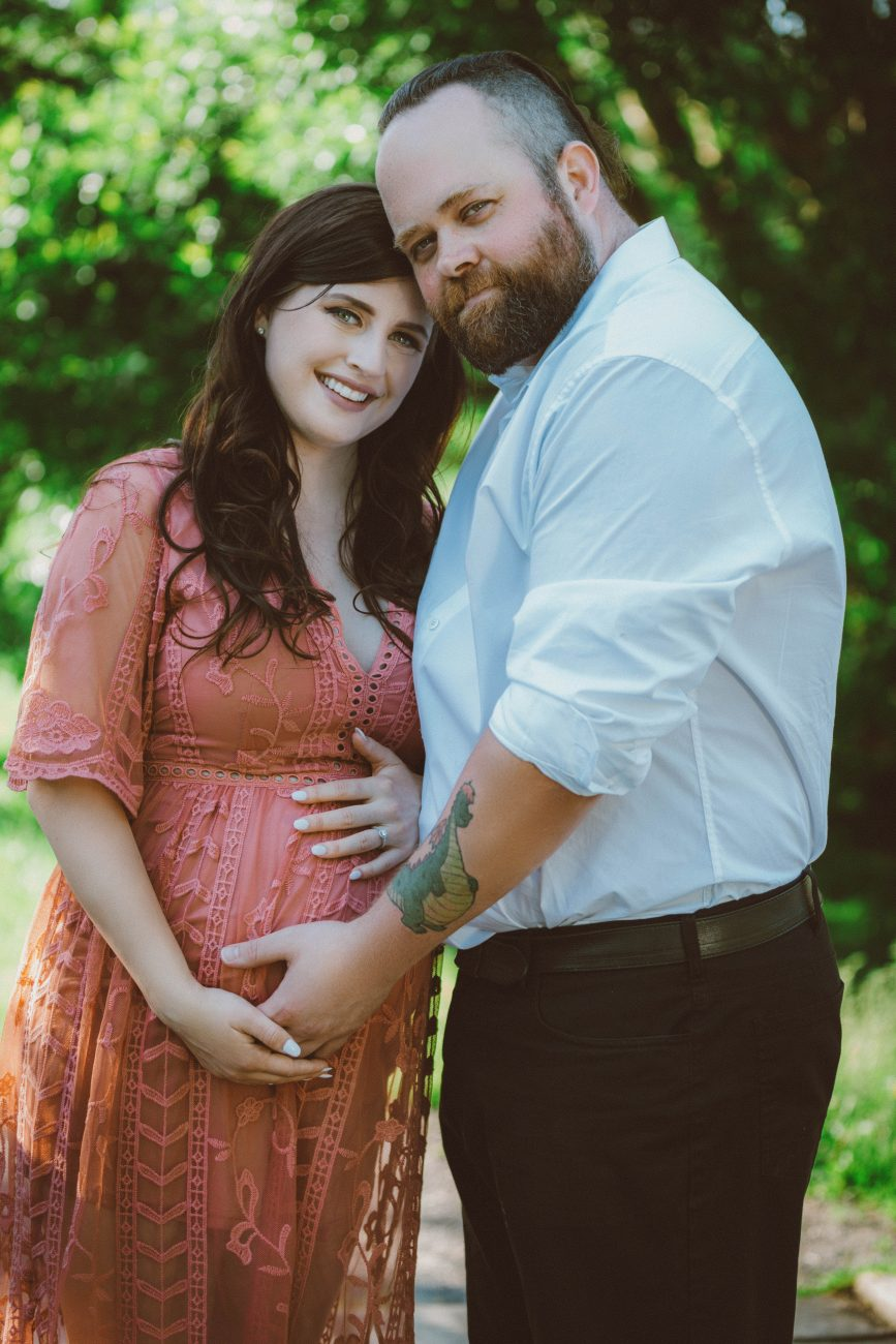 Summer maternity portrait of a married couple embracing and smiling