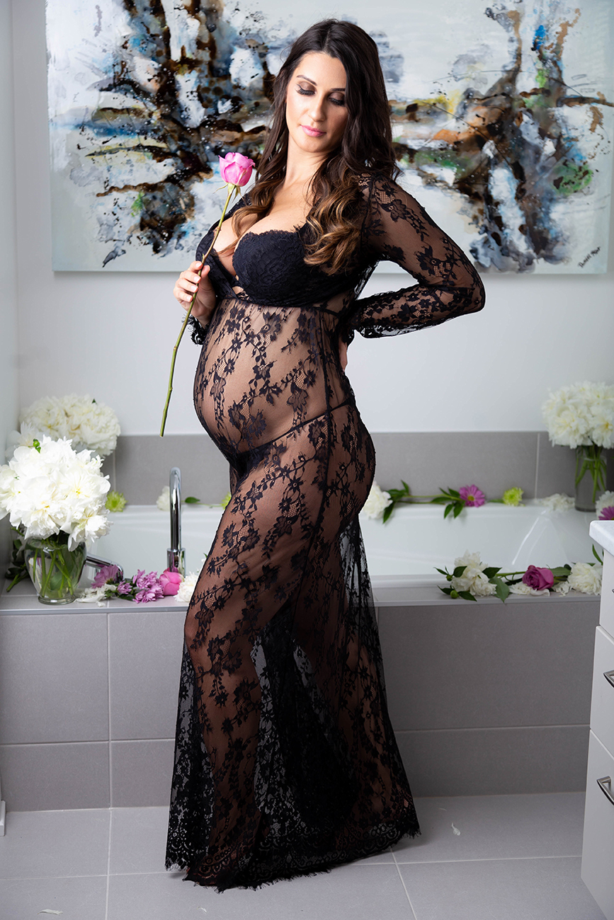 Portrait of a pregnant woman standing in the bathroom smelling a flower wearing a black lace dress