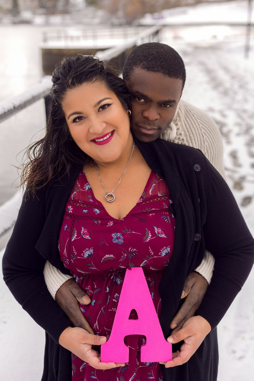 Winter maternity portrait of couple hugging and holding her pregnant belly