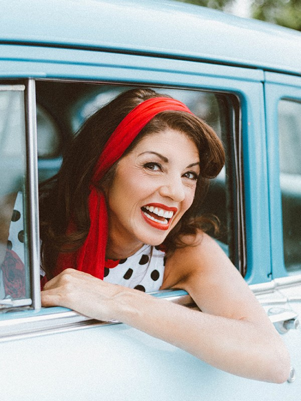 vintage portrait of a mature model wearing 1950s fashion in a vintage car