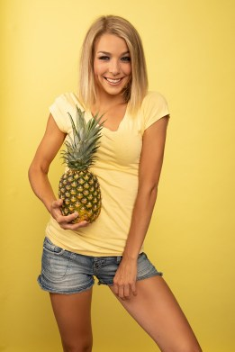 Smiling blonde model holding a pineapple in a studio portrait