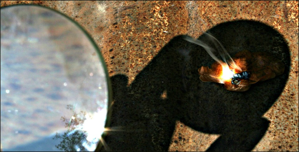 Starting a fire with a magnifying glass.