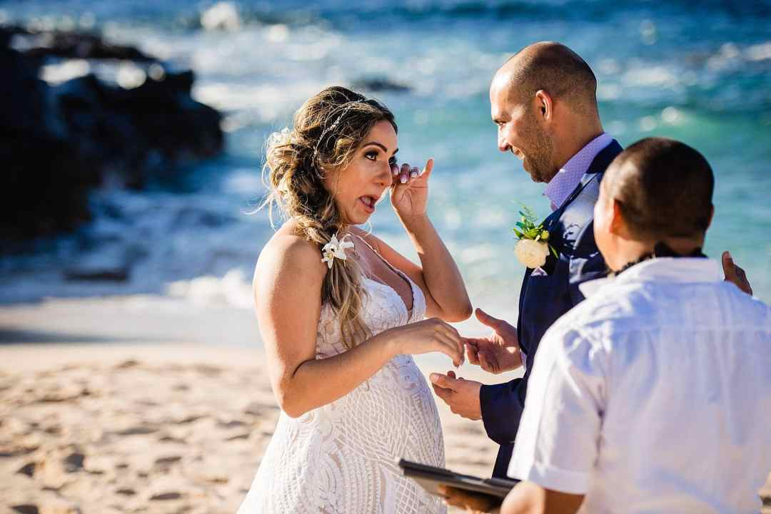 bride wiping tears at beach ceremony