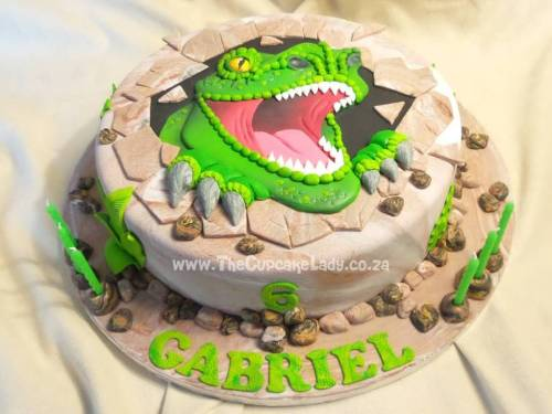 Single tier vanilla cake with chocolate butter icing, decorated with a sugar paste cover to look like stone, with a 2D sculpted sugar paste T-Rex coming through the rock and sugar paste stones and plants on the sides