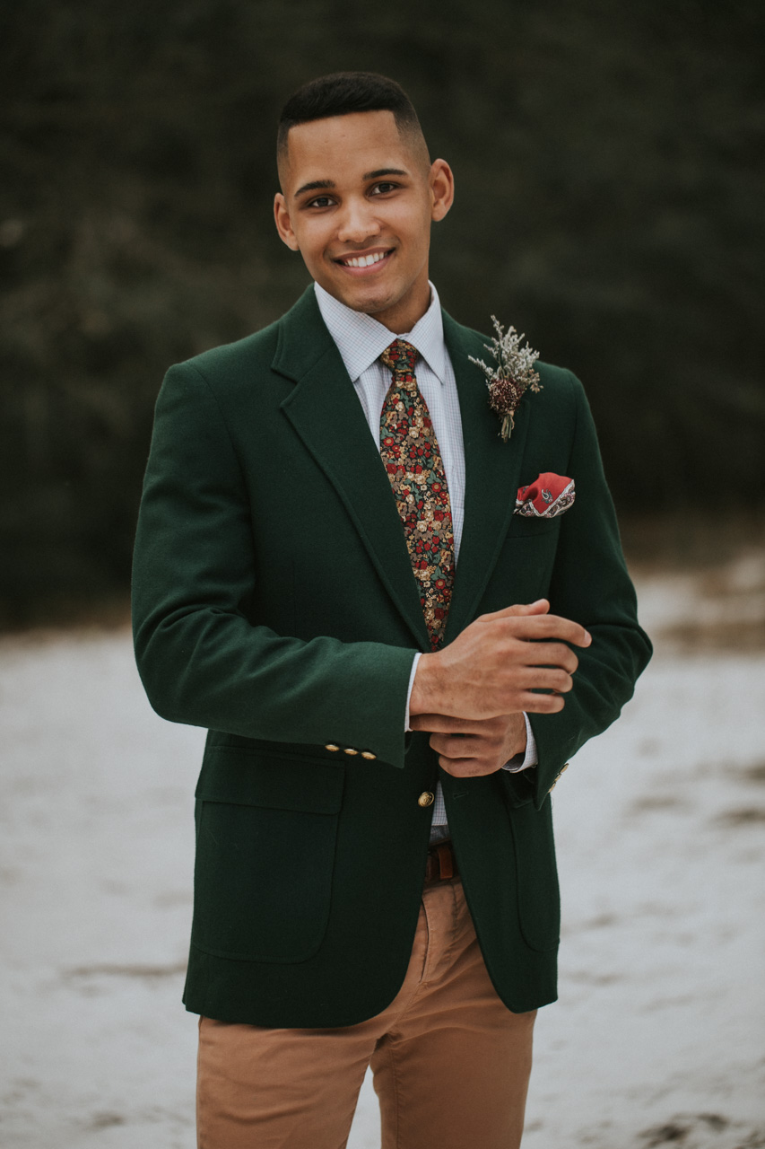 Groom wearing forest green suit jacket at Lake Runnymede in St. Cloud Florida