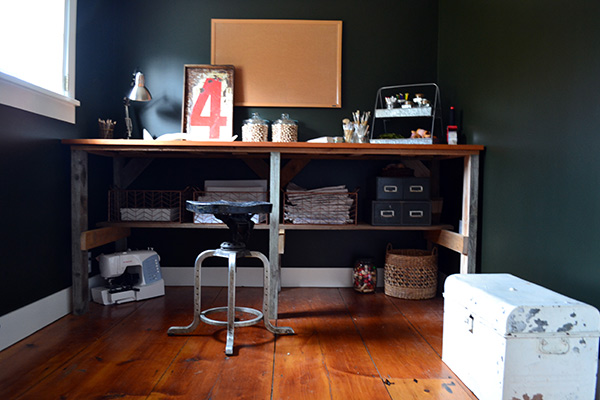 Black craft room with rustic wood desk and wide pine floors