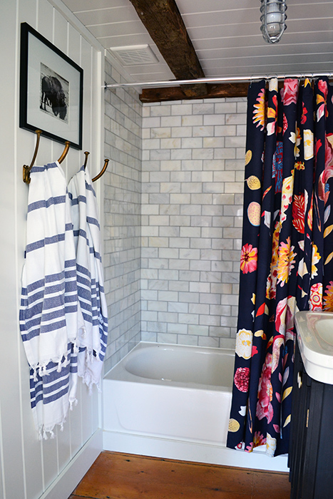 Bathroom renovation reveal. Decorating with an Anthropologie shower curtain and blue striped Turkish bath towels.