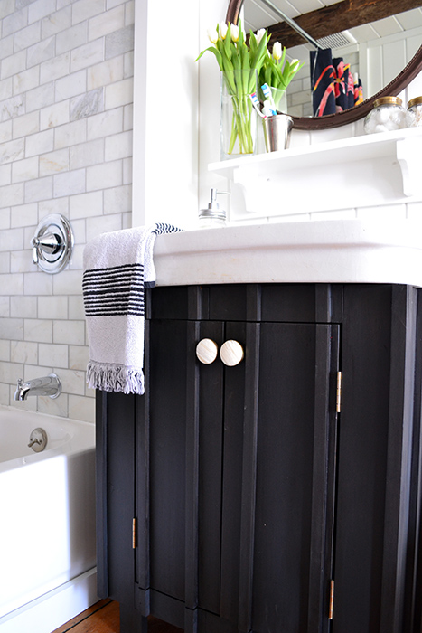During this bathroom renovation, a sink base was chalk painted in Annie Sloan's graphite, finished with a dark wax, and accented with round white and gold knobs from Hobby Lobby.