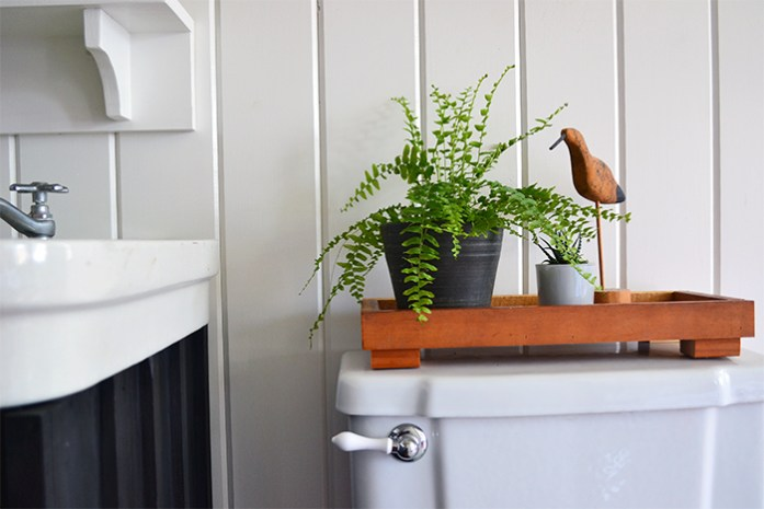 A small wooden tray sits on the back of this farmhouse toilet, holding a fern, small succulent in a blue glass pot, and a wooden sand piper accessory.