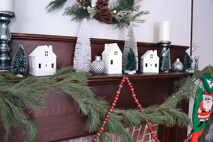 Simple Christmas decor featuring vintage wood beads, pine swag, and Target ceramic houses