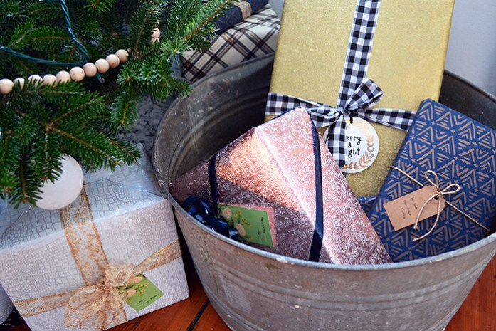 Christmas presents wrapped in a mix of pink, gold, and navy blue wrapping paper