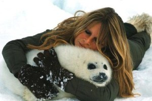 Early iconic image of Brigitte Bardot posing with seal pup.