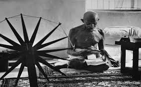 Mohandas Gandhi spinning cotton during his own time as a back-to-the-earther.